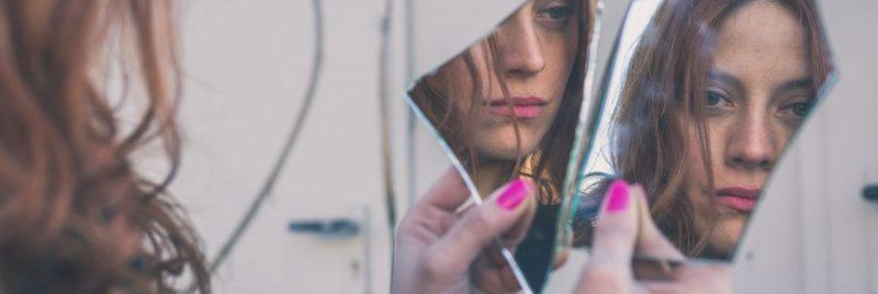 Mulher se olhando num pedaço de espelho quebrado