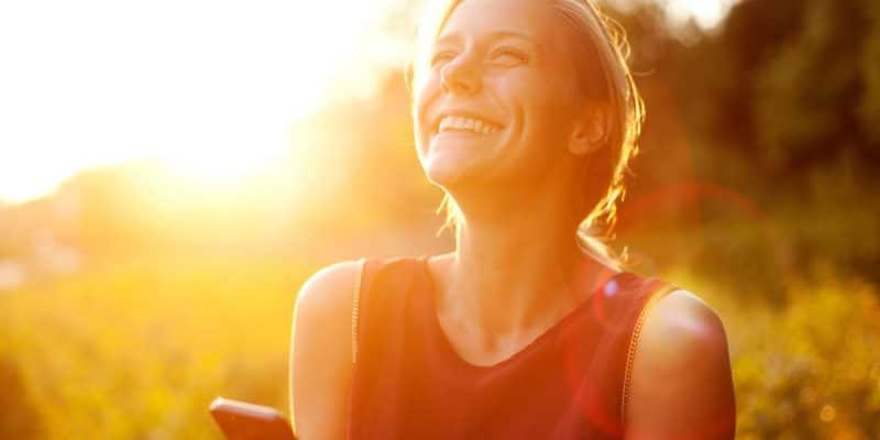 Mulher sorrindo com sol de fundo segurando celular