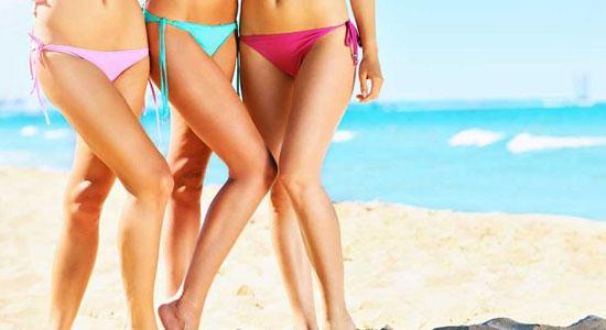 Mulheres de biquini, mostrando as pernas na praia